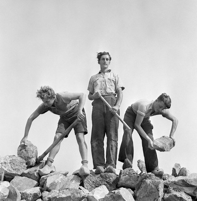 Roman Vishniac. '[Ernst Kaufmann, center, and unidentified Zionist youth, wearing clogs while learning construction techniques in a quarry, Werkdorp Nieuwesluis, Wieringermeer, The Netherlands]' 1939