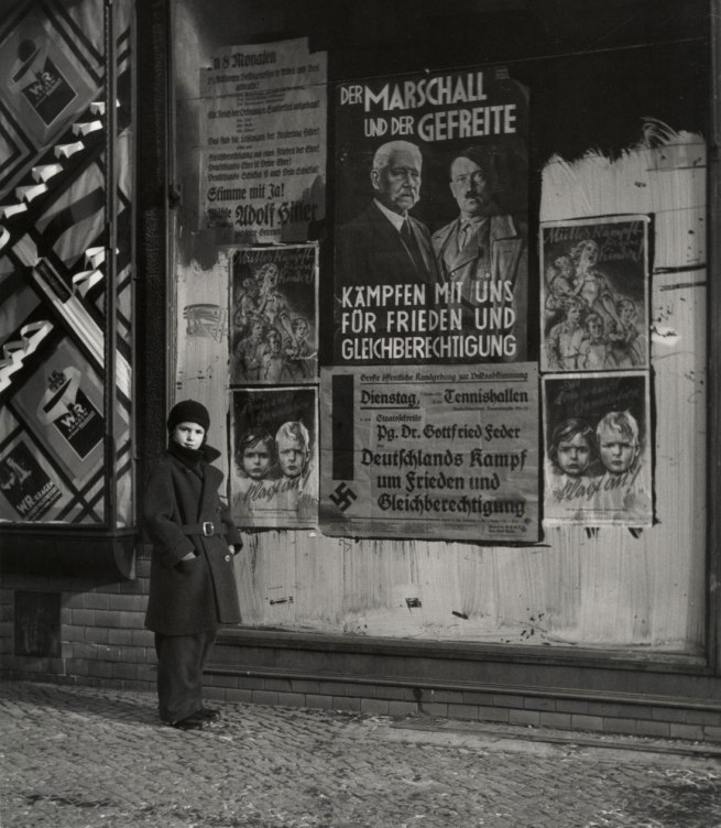 "Roman Vishniac. '[Vishniac's daughter Mara posing in front of an election poster for Hindenburg and Hitler that reads ""The Marshal and the Corporal: Fight with Us for Peace and Equal Rights,"" Wilmersdorf, Berlin]' 1933"