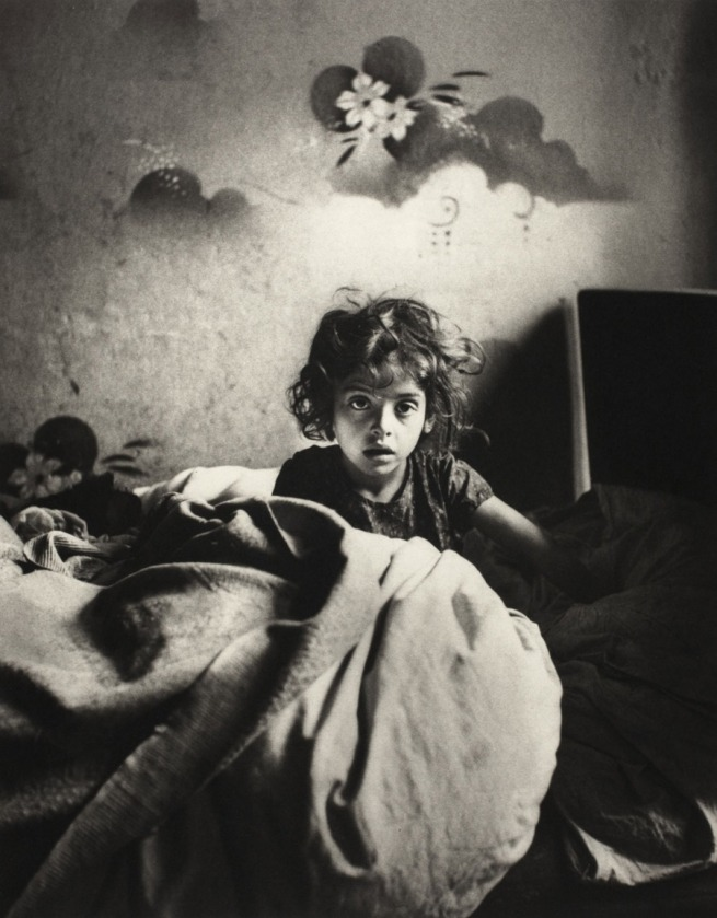 Roman Vishniac. '[Sara, sitting in bed in a basement dwelling, with stenciled flowers above her head, Warsaw]' c. 1935-37