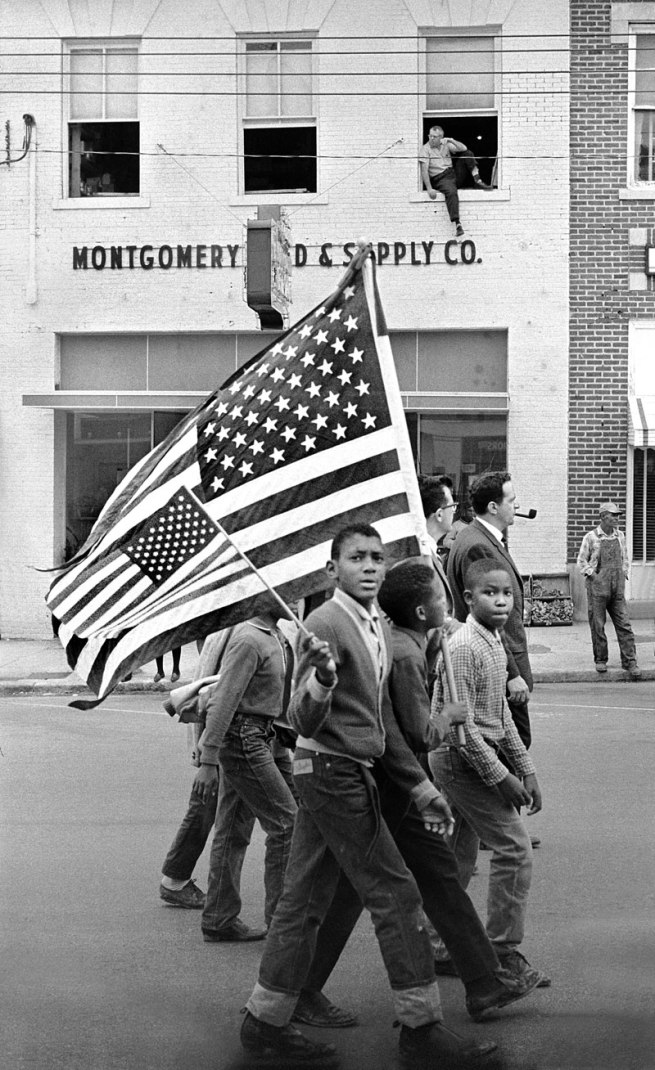 Stephen Somerstein. 'Young civil rights marchers with American flags march in Montgomery' 1965