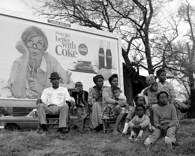 """Stephen Somerstein. '""""Things Go Better With Coke"""" sign and multi-generational family watching marchers' 1965"""