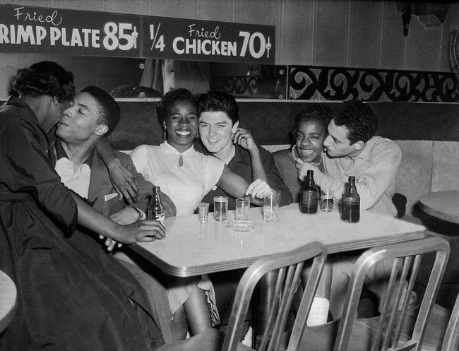 "Charles ""Teenie"" Harris (1908-1998) 'Three men and three women, seated as couples in banquette in bar or restaurant advertising ""Fried Shrimp Plate $.85"" and ""1/4 Fried Chicken $.70""' c. 1959; printed 2001"