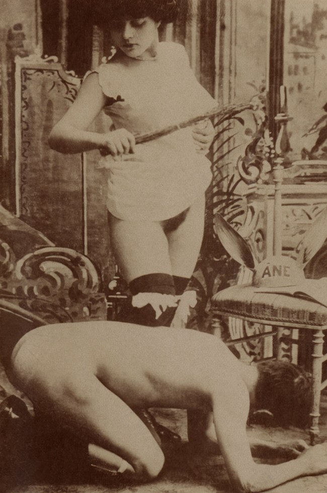 Unknown photographer (France) 'Woman holding a birch rod over a kneeling nude man' 1890-1900
