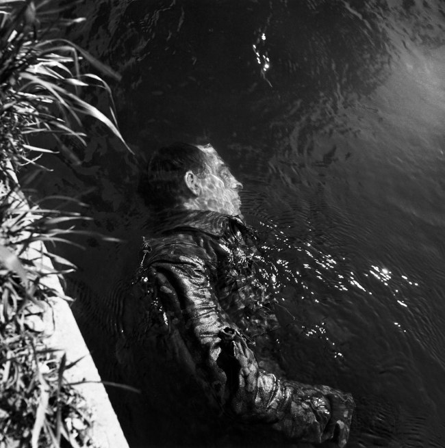 Lee Miller. 'SS Guard in Canal, Dachau, Germany' 1945