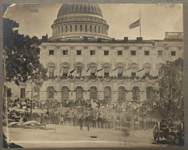 Mathew B. Brady. 'Untitled [Spectators massing for the Grand Review of the Armies, 23-24 May 1865, at the side of the crepe-draped U.S. Capitol, flag at half mast following the assassination of President Abraham Lincoln]' 1865