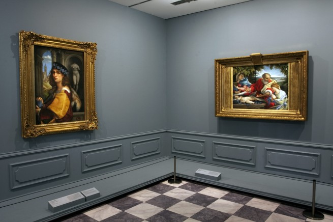 Installation view of room 2 of the exhibition 'Masterpieces from the Hermitage: The Legacy of Catherine the Great' at NGV International, Melbourne featuring to the left, Domenico Capriolo (Italian c. 1494-1528) 'Portrait of a young man' 1512 and to the right, Lorenzo Lotto (Italian c. 1480-1556) 'The Rest on the Flight into Egypt with Saint Justine' 1529-30