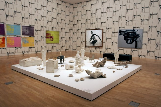 Installation view of the sixth room with, on the floor, Ai Weiwei's 'S.A.C.R.E.D. Maquettes' (2011) with Andy Warhol's 'Gun' (1981-82) paint and silkscreen ink on linen work on the wall behind