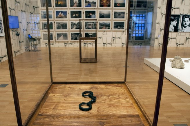 Installation view of Ai Weiwei's 'Handcuffs' (2015) in the sixth room of the exhibition with his 'Study of Perspective' (1995-2011) series of photographs on the wall behind