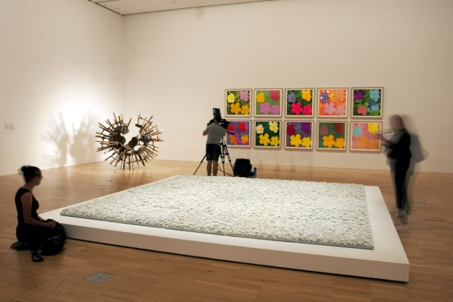 Installation view of the fourth room including, at centre, Ai Weiwei's 'Blossom' (2015) with his 'Grapes' (2011) rear left, and Andy Warhol's 'Flowers (Hand Coloured)' (1974) on the wall behind