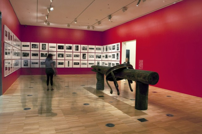 Installation view of second room including, at centre, Ai Weiwei's 'Pillar through Round Table' (2004-5) with Ai's black and white photographs behind