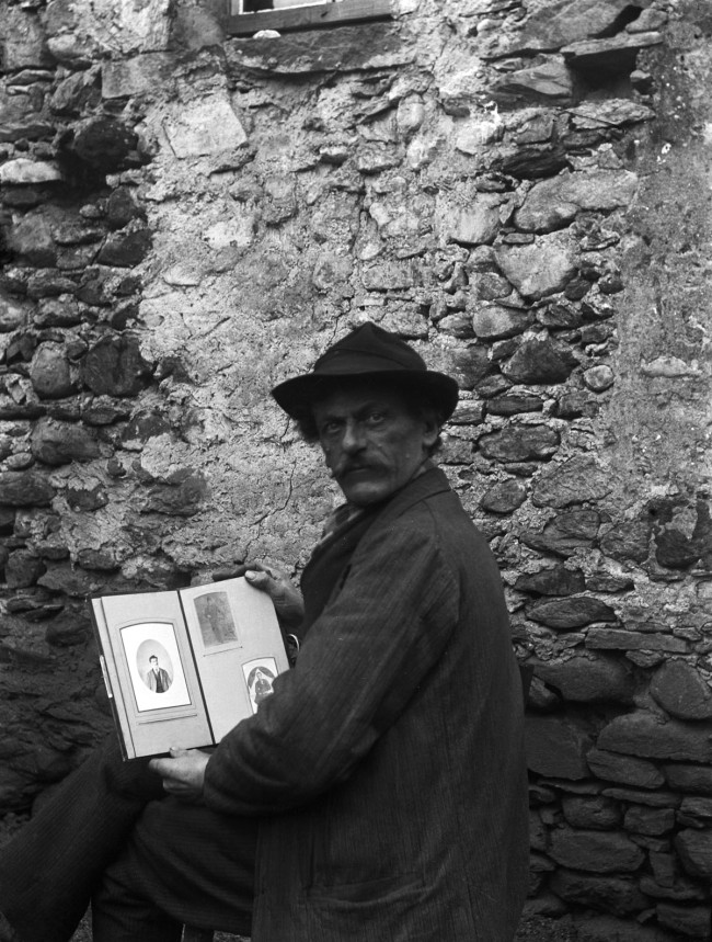 Roberto Donetta. 'Self-portrait of Roberto Donetta with hat and a photo album in hand, in front of a wall, Bleniotal' 1900-1932