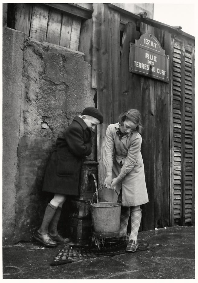 Sabine Weiss. 'Enfants prenant de l'eau à la fontaine, rue des Terres-au-Curé' Paris, 1954