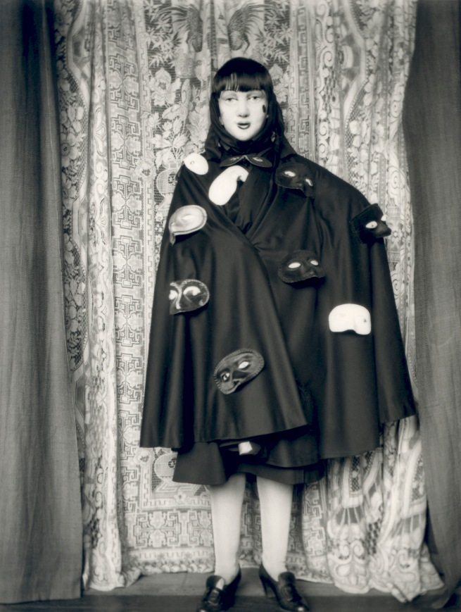 Claude Cahun. 'Self-portrait (full length masked figure in cloak with masks)' 1928