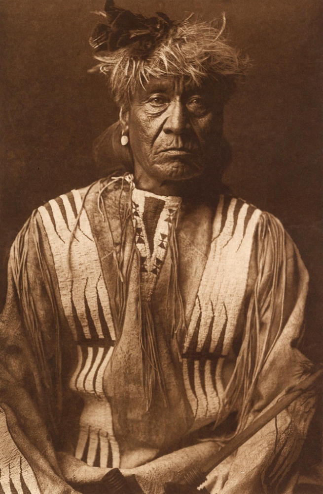 Edward S. Curtis (1868-1952) '[Atsina Indian, Red Whip, half-length portrait, seated, facing front, wearing feather, beaded buckskin shirt, holding pipe in left hand]' c. 1908