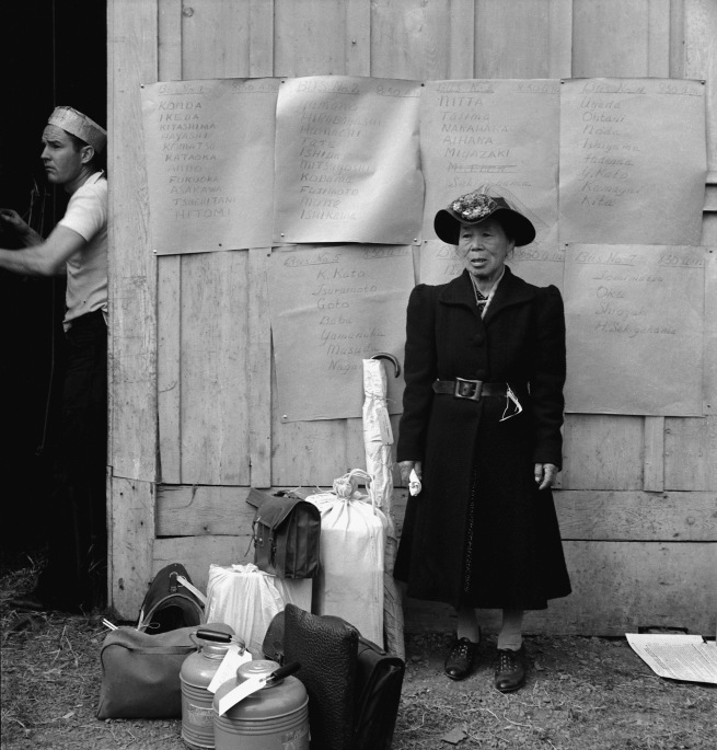 Dorothea Lange. 'Centerville, California. This evacuee stands by her baggage as she waits for evacuation bus' 1942
