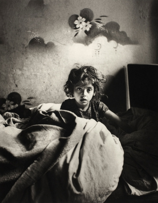 Roman Vishniac (1897-1990) 'Sara, sitting in bed in a basement dwelling, with stencilled flowers above her head, Warsaw' c. 1935-37