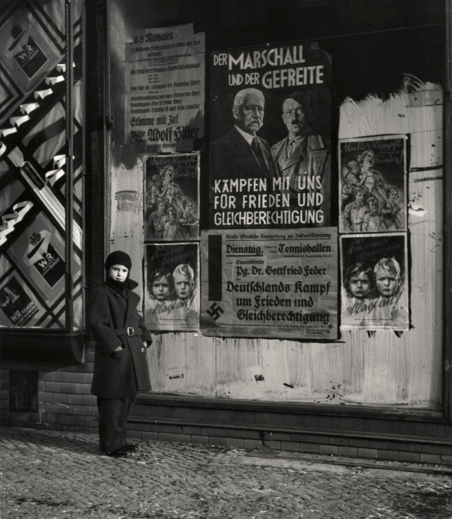 Roman Vishniac (1897-1990) 'Vishniac's daughter Mara posing in front of an election poster for Hindenburg and Hitler' 1933