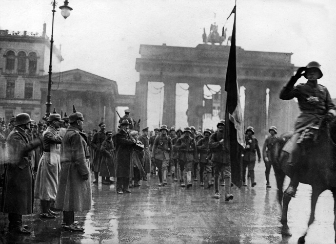 "Willy Römer (German, 1887-1979) '""The Guards Ranger Battalion marching past General Lequis""; on the left, next to the Brandenburg Gate, the photographer Walter Gircke with camera' 10/11 December 1918"