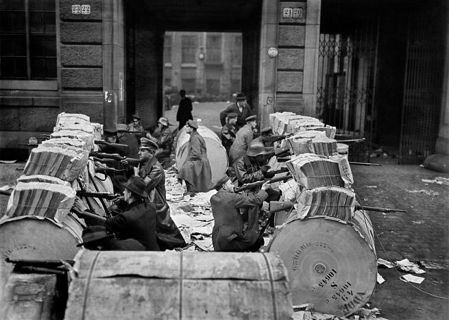 Willy Römer (German, 1887-1979) 'Spartacists behind barricades made from rolled newspaper in front of the Mosse building (Berliner Tageblatt) on Schützenstraße at the corner of Jerusalemerstraße' 11.1.1919