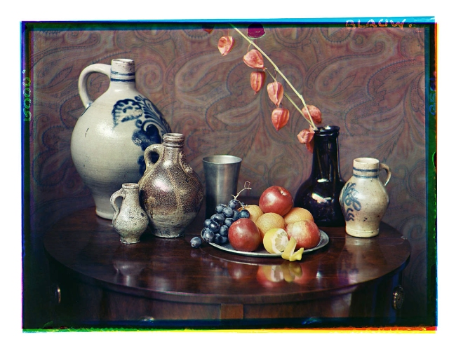 Bernard F. Eilers (1878-1951) 'Stilleven met steengoed kannen, fruit, tingoed en gedroogde bloemen van een lampionplant in een fles' (Still life with stoneware jugs, fruit, tin goods and dried flowers of a lantern plant in a bottle) 1934-04/1934-12