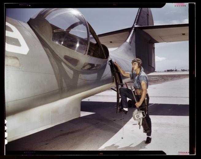 Howard R. Hollem (American, -1949) for the United States Office of War Information. 'Jesse Rhodes Waller, a World War II Aviation Ordnanceman stationed at the Naval Air Station in Corpus Christi, Texas, installing a M1919 Browning machine gun in a United States Navy PBY plane' August 1942