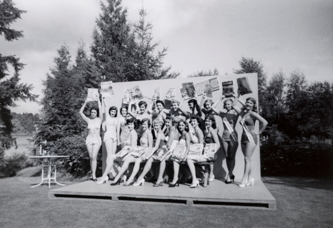 Photographer Unidentified (American) 'Untitled (seventeen women in swimsuits hold magazines up on a low stage on a lawn)' 20th century (c. 1950s)