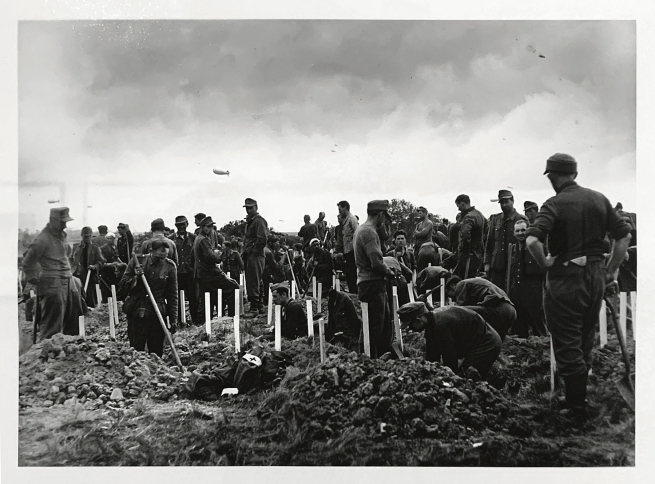 Robert Capa (American-Hungarian, 1913-1954) 'German soldiers captured by American forces burying some of the men killed during the D-Day landings, near Colelville-sur-Mer, Omaha Beach, Normandy, France' June 1944