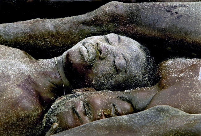 Carolyn Cole (American, b. 1961) 'Dozens of bodies are laid in a mass grave on the outskirts of Monrovia, Liberia' August 2003