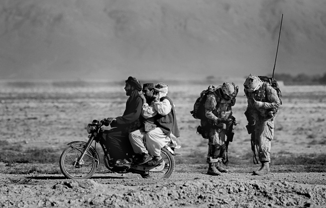 Anja Niedringhaus (German, 1965-2014) 'Afghan men on a motorcycle overtake Canadian soldiers' September 2010