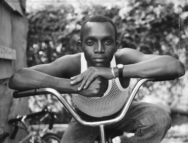 Dawoud Bey (American, b. 1953) 'A Young Man Resting on an Exercise Bike, Amityville, NY, 1988' 1988