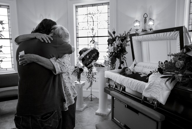 James Nachtwey (American, b. 1943) 'Cheryl Schmidtchen, 67, being consoled at the funeral for her granddaughter Michaela Gingras in Manchester, N.H., on September 17th, 2017. Gingras, a heroin user, was 24' 2017
