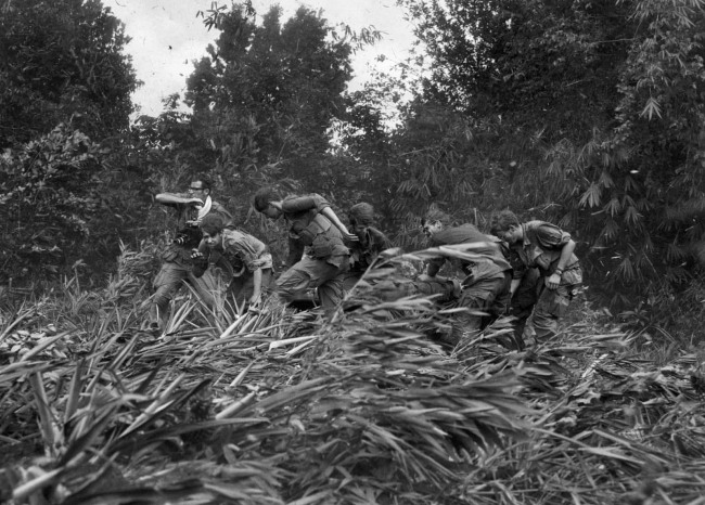 Henri Huet (French, 1927-1971)/AP ''Life' magazine photographer Larry Burrows (far left) struggles through elephant grass and the rotor wash of an American evacuation helicopter as he helps GIs carry a wounded soldier on a stretcher from the jungle to the chopper in Mimot, Cambodia' 4 May 1970