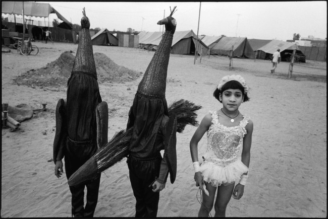 Mary Ellen Mark (American, 1940-2015) 'Child Acrobat with Two Children in Peacock Costumes, Great Royal Circus, Himmatnagar, India' 1989 (printed later)