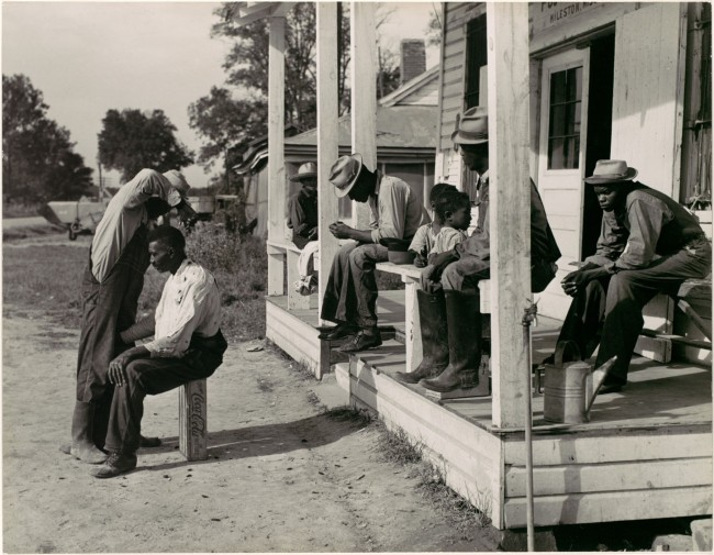 Marion Post Wolcott (American, 1910–1990) '[Haircutting in Front of General Store and Post Office on Marcella Plantation, Mileston, Mississippi]' 1939