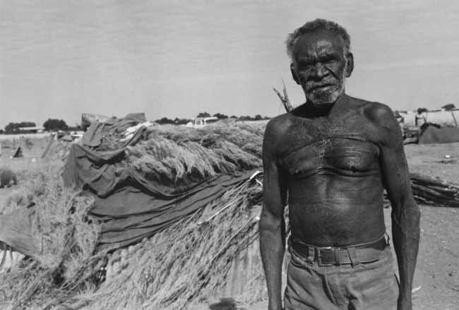 Mervyn Bishop (Australian, b. 1945) 'Aboriginal man beside humpy, Yuendumu, Northern Territory' 1974, reproduction 2014
