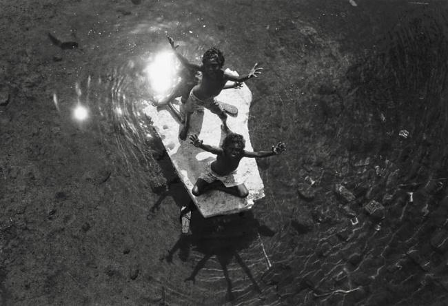 Mervyn Bishop (Australian, b. 1945) 'Children floating on board, Yirrkala, Northern Territory' 1989, reproduction 2014